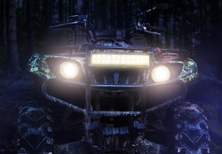 Photo of a camouflaged dirty offroad hunting atv vehicle standing at night in forest with headlights turned on, front view.