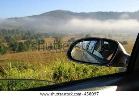 Photo of a car driving in the country.