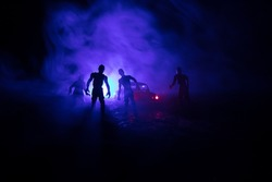 photo of a car stopped on the road lighting up a zombies. Silhouette terrible zombie night near the car. Miniature decoration. Selective focus