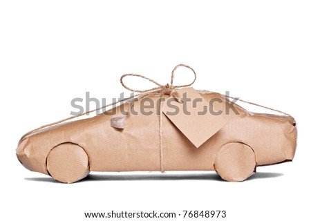 Photo of a car wrapped in brown recycled paper with label, cut out on a white background.