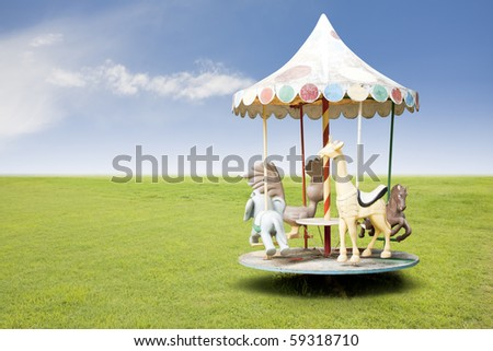 photo of a carousel for kids on grass field