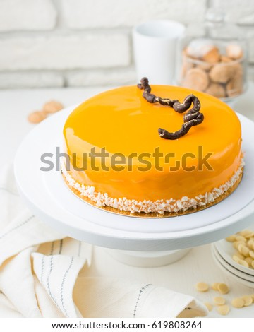 Photo of a carrot honey mousse cake in a cafe. A modern cake with a cut piece. Light background, white brick wall, light dishes and cake stand. The atmosphere of the coffee house. sweet photo