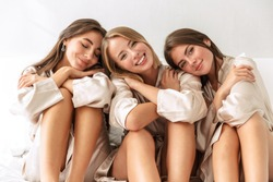 Photo of a cheery optimistic positive young girls women friends indoors on bed at the hen party at home.