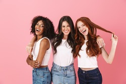 Photo of a cheery smiling positive young three multiethnic girls friends posing isolated over pink wall background.