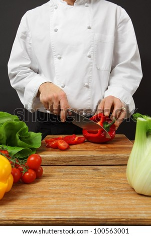 Photo of a chef chopping vegetables on a wooden cutting board.