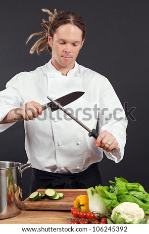 Photo of a chef with dreadlocks sharpening his chopping knife.