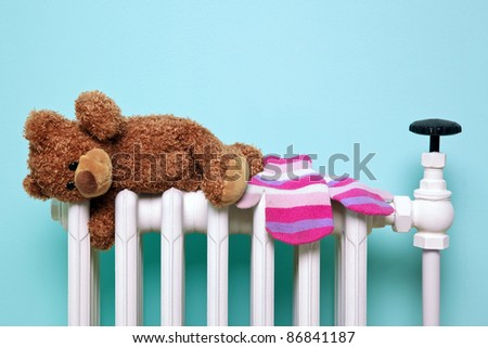 Photo of a childs teddy bear and woolen mittens drying on an old traditional cast iron radiator, good image for winter and childhood themes. The bear is a generic non-brand bear, FYI he\'s called Bob!