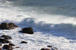 Photo of a choppy coastline with a foamy wave crashing against the rocks