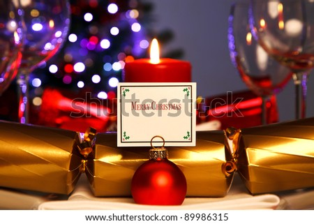 Photo of a Christmas dinner place setting and bauble card holder with decorated tree out of focus in the background. Lit by candlelight. - stock photo