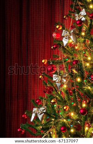 Photo of a Christmas tree next to red window curtains with copy space