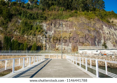 Photo of a cliff with vegetation, white railing and sunlight #1146441788