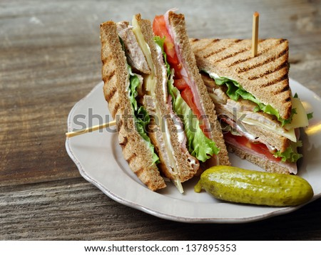 Photo of a club sandwich made with turkey, bacon, ham, tomato, cheese, lettuce, and garnished with a pickle.
