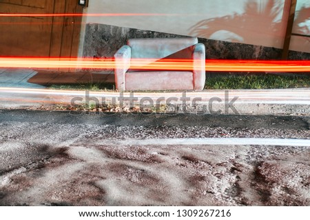 Photo of a couch left on a sidewalk at night with cars passing by