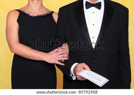 Photo of a couple in black tie evening wear, the man is holding an invitation.