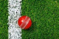 Photo of a cricket ball on a grass next to the white line, shot from above.