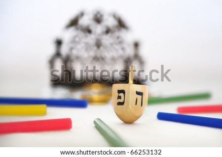 Photo of a dreidel (spinning top), a bronze menorah, and colorful candles isolated on white - objects for the Jewish holiday of Hanukkah