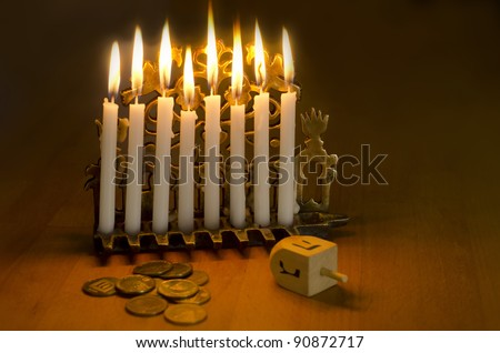 Photo of a dreidel (spinning top), gelts (candy coins) and an ancient brass menorah for the Jewish holiday of Hanukkah.