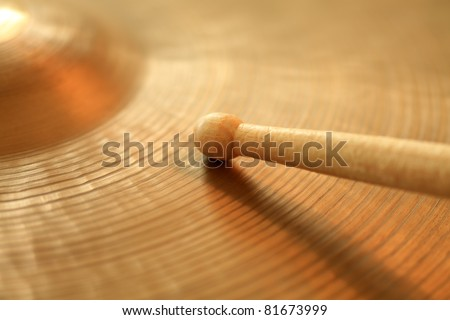 Photo of a drumstick playing on a hi-hat or ride cymbal.  Focus on tip of stick.