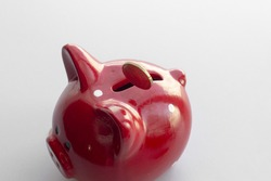 Photo of a falling euro coin into the slot of a piggy bank. The concept of saving or save money or open a bank deposit or income related to saving money