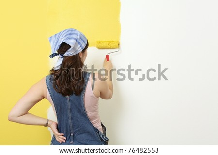 Photo of a female painting a wall with a roller and yellow paint.