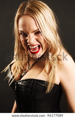 Photo of a female vampire with mouth open and fangs showing.  Harsh lighting and shadows for scarier feel.