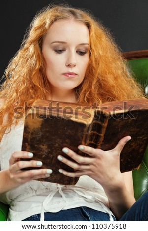 Photo of a female with red curly hair reading an old book.