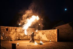 photo of a fire show performer playing with fire