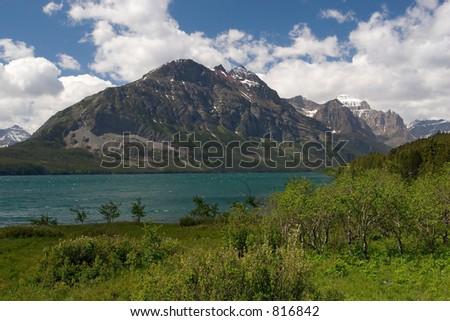 Photo of a foliage, Saint Mary Lake and sharp peaks at Glacier National Park in Montana