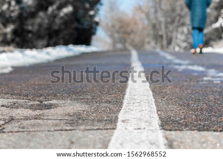 Photo of a fragment of an asphalt road with a white stripe in focus and a walking man in defocus. The rest of the frame is defocused, for use as a background. #1562968552