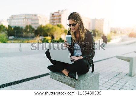 Photo of a freelancer female enjoying take away coffee while working outdoors on a portable computer connected to public wifi. Stylish student girl studying online while spending free time in a park