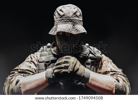 Photo of  Photo of a fully equipped camouflaged soldier in panama hat posing with fists on dark background wirh fog.