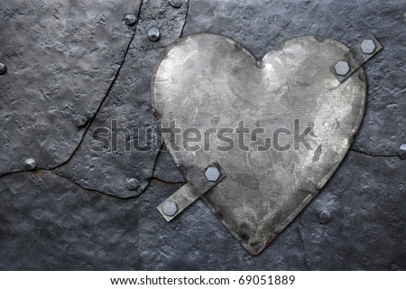 Photo of a galvanized metal heart bolted to old hammered metal plates with rivets. - stock photo