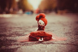 Photo of a gentle, sad handmade doll in a red dress and sitting on the road
