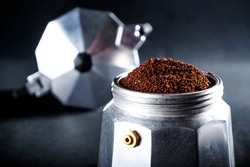 Photo of a geyser coffee maker with ground coffee. Freshly brewed coffee.