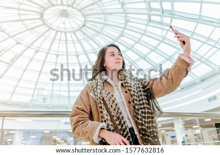 Photo of A girl blogger in a shopping center takes pictures, takes a selfie, broadcasts live, communicates with followers