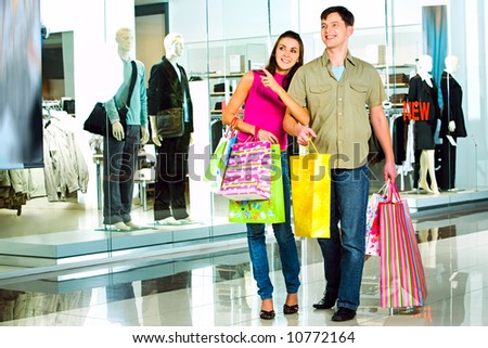 Photo of a girl looking attentively and pointing at something in the shopping centre with handsome man near by