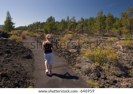 Photo of a girl walking through lava rocks at the Lava Cast Forest, Newberry National Volcanic Monument, near Bend, Oregon, USA