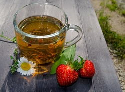 Photo of a glass mug with green tea, berries and flowers on a wooden table. Photography of tea, tea drinking