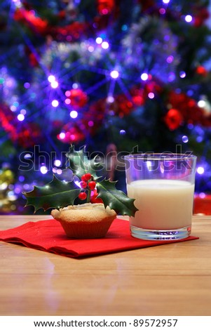 Photo of a glass of milk and a mince pie with holly on top on a table, left out on Christmas eve for Santa, Christmas tree in the background with fairy lights and decorations.