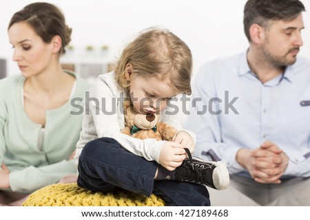 Photo of a gloomy young family with a sad little boy hugging a teddy bear, and his parents with depressed looks #427189468