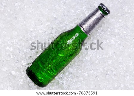 Photo of a green glass bottle of beer on crushed ice.
