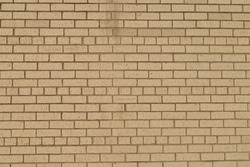 Photo of a grunge tan brick wall taken outdoors on a sunny day