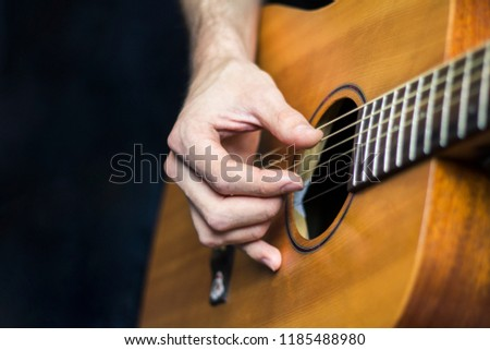 Photo of a hand playing the yellow wooden acoustic guitar with it's fingers on dark background close up