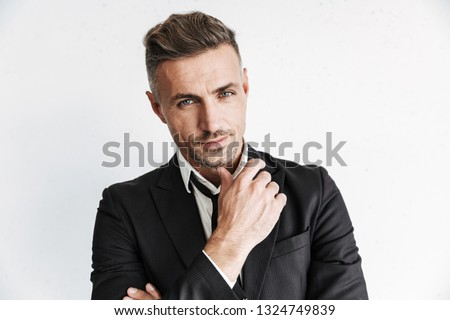 Photo of a handsome business man posing isolated over white wall background.
