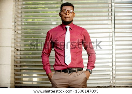Photo of a handsome young handsome businessman outdoors in the street near the business center posing looking aside.