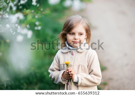 Photo of a happy child, a small blonde girl in nature, on a walk, near a cherry blossoming, spring garden, in a coat