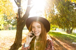 Photo of a happy pleased cutie young student redhead girl in autumn park talking by mobile phone.