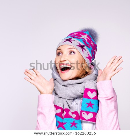 Photo of a happy surprised woman in winter clothes with bright positive emotions looking up - at studio