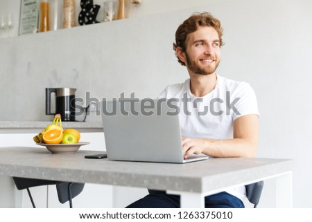 Photo of a happy young bearded man at the table at home talking using laptop computer.