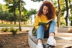 Photo of a happy young beautiful curly student girl sitting outdoors in nature park writing notes in notebook.